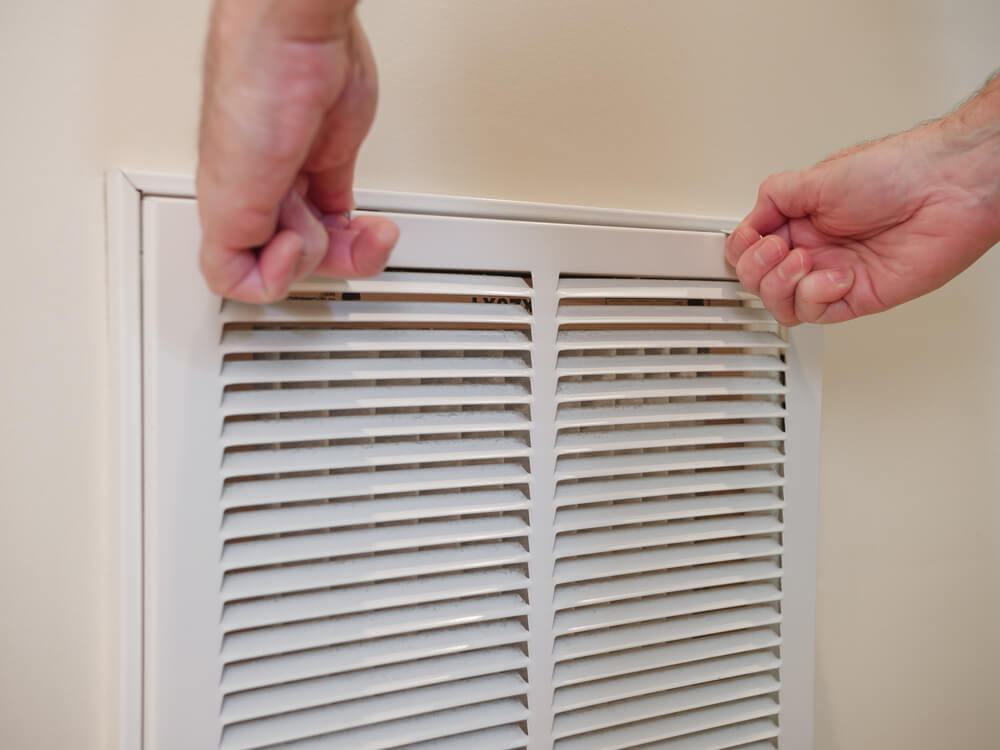 person changing their hvac filter to prevent allergies in their home