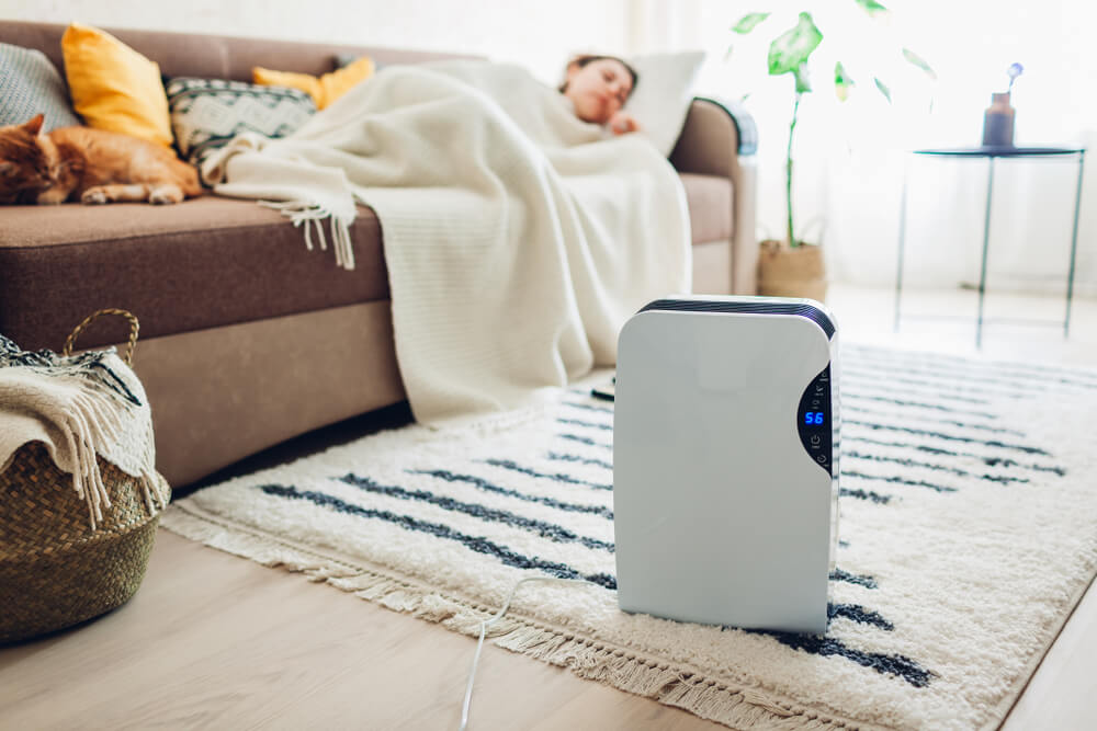 woman laying on the couch using a dehumidifier to prevent allergies