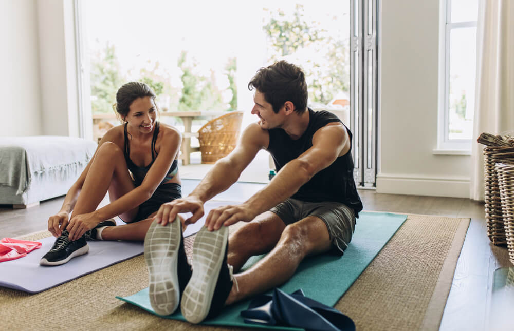man and woman exercise together on yoga mats