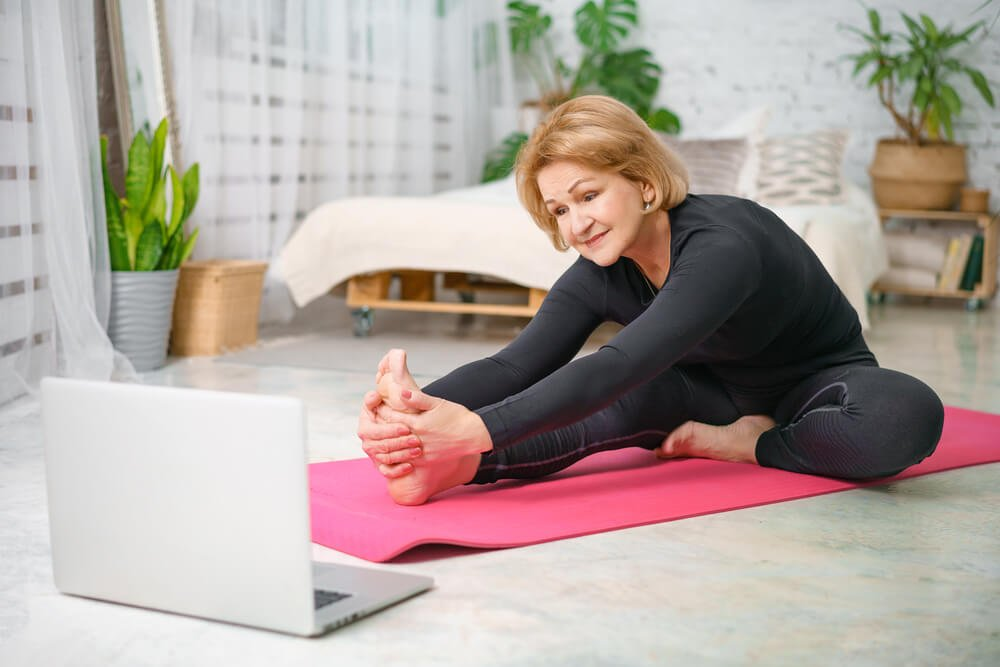 woman watches online resource on laptop while exercising