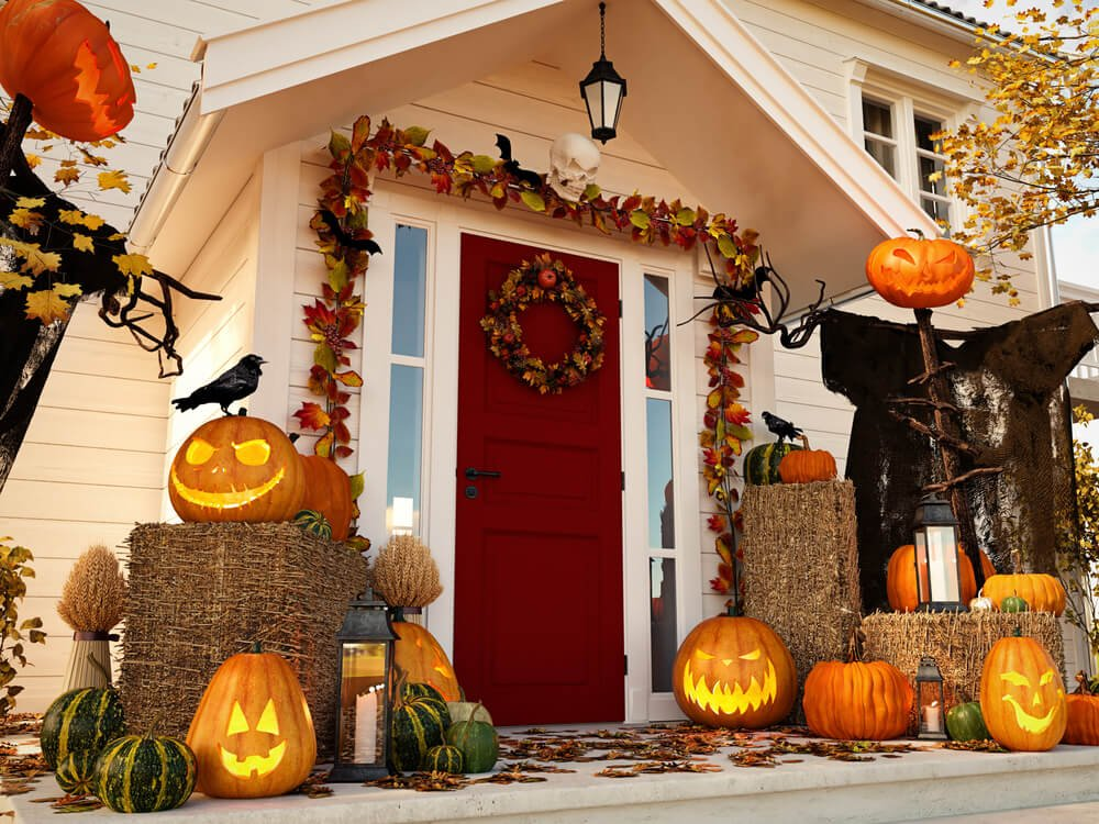 front of house decorated with pumpkins, leaves, and hay bales for halloween