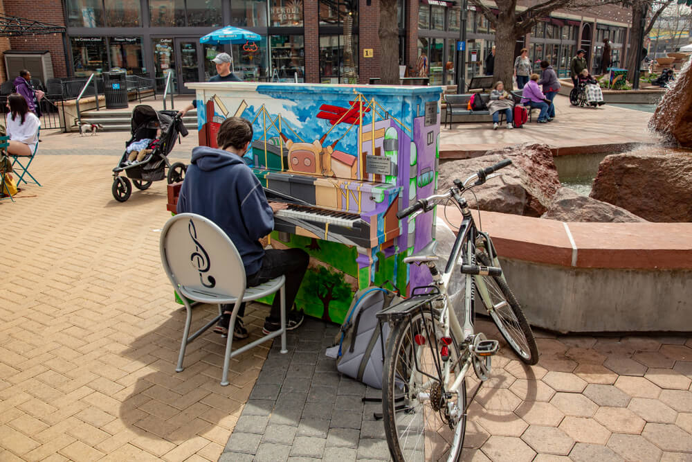 man playing painted piano in old town square fort collins