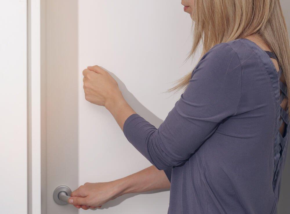 woman landlord knocking on bedroom door before entering