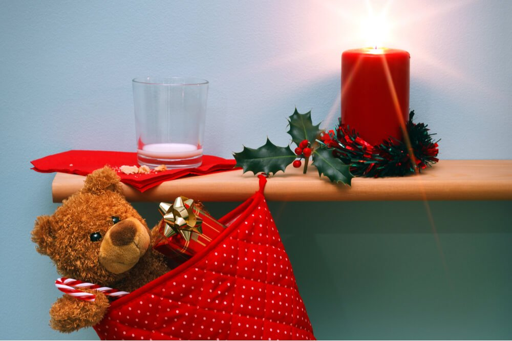 Christmas stocking holding a teddy bear hangning from shelf with lit candle and empty glass of milk