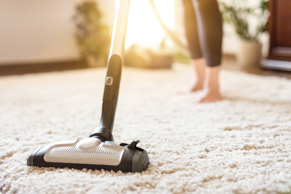 woman vacuuming carpet to prevent allergies in her home